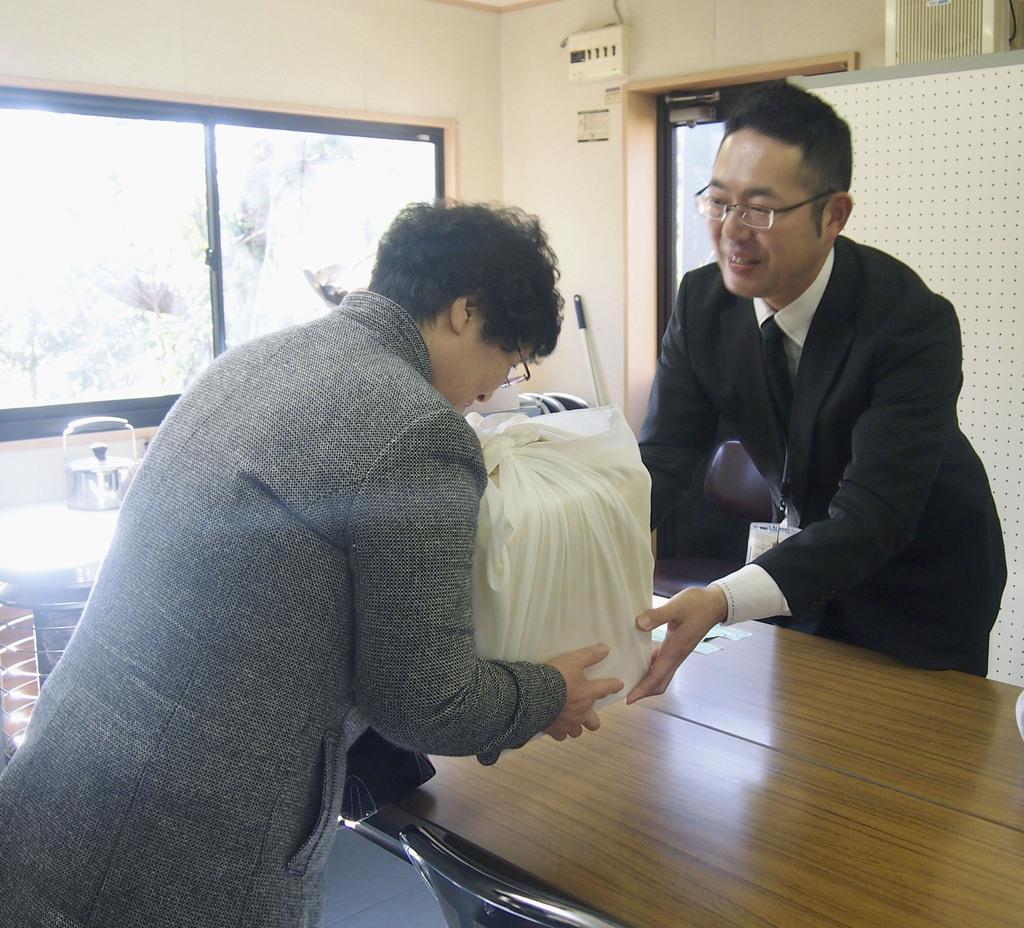 東日本大震災で犠牲になった近藤あさのさんの遺骨を受け取る遺族(左)=29日午前、宮城県石巻市
