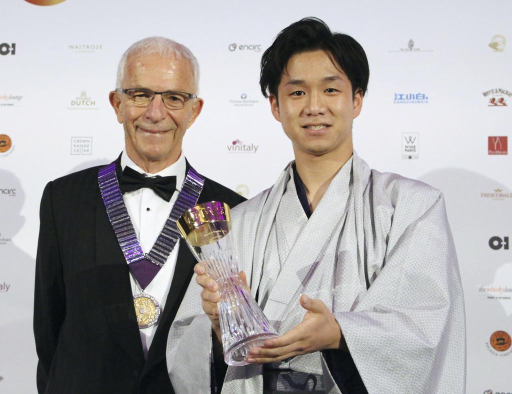 ロンドンで開かれた世界的な酒類コンテストの式典で表彰される浜田酒造の浜田光太郎さん(右)=28日(共同)