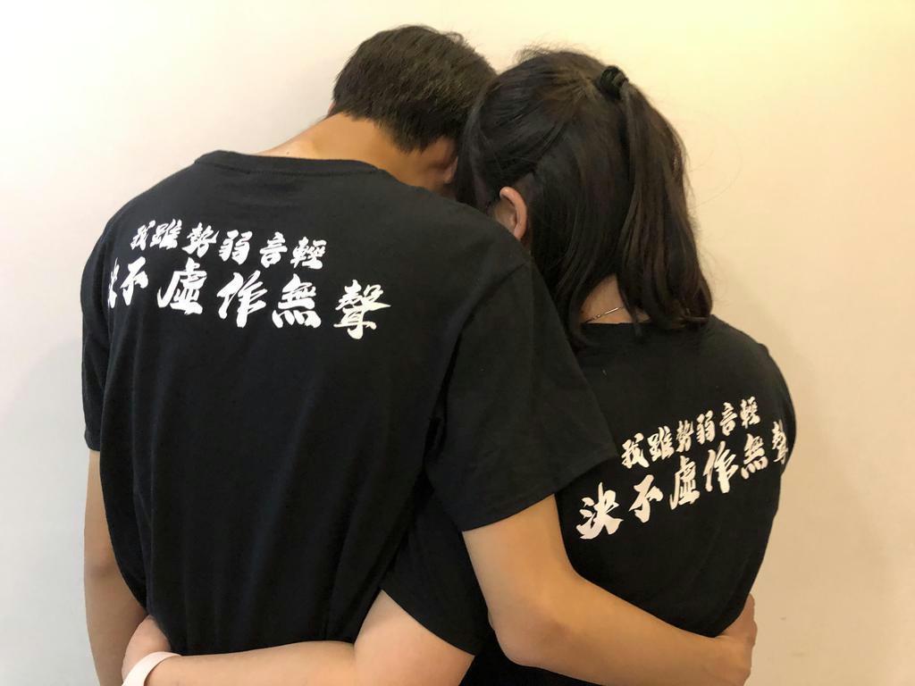 「声は小さいが決して黙らない」と書かれたシャツを着る2人