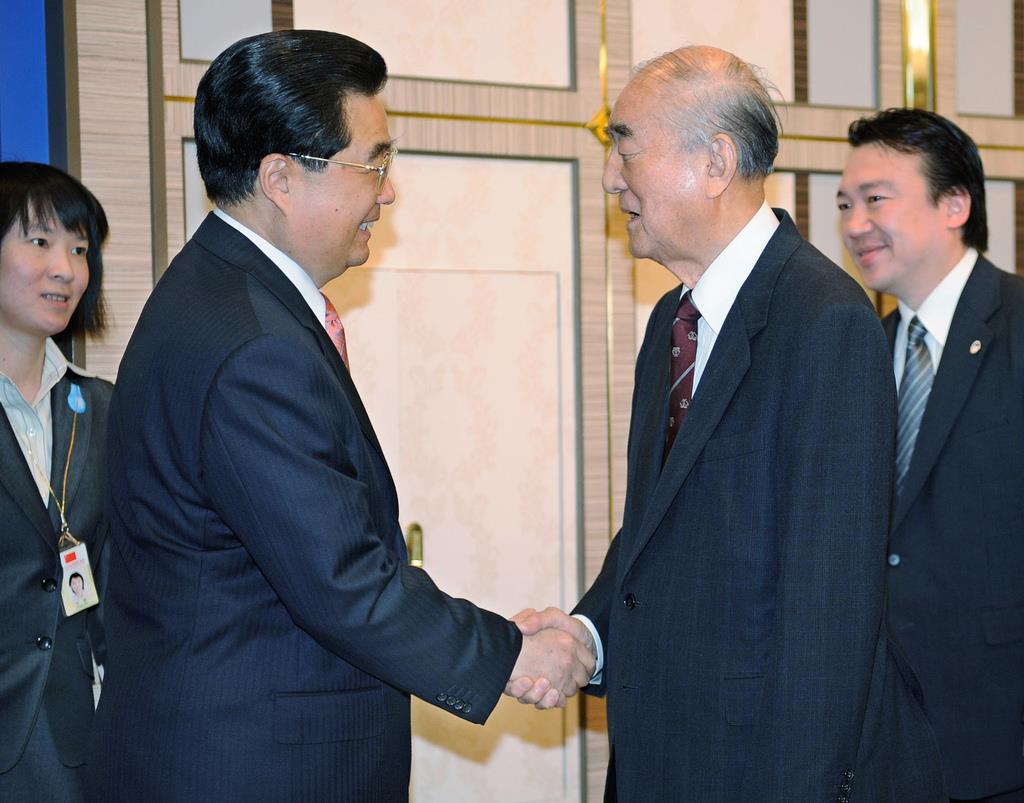 2008年5月、中国の胡錦濤国家主席(手前左)と握手を交わす中曽根康弘元首相=東京(AP)