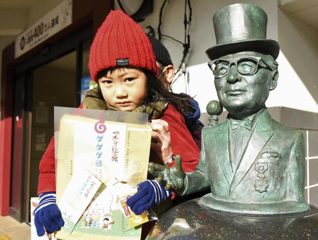 水木しげる記念館で配られた「ゲゲゲ忌」の特別入場券や記念品を手にする女の子=11月30日、鳥取県境港市