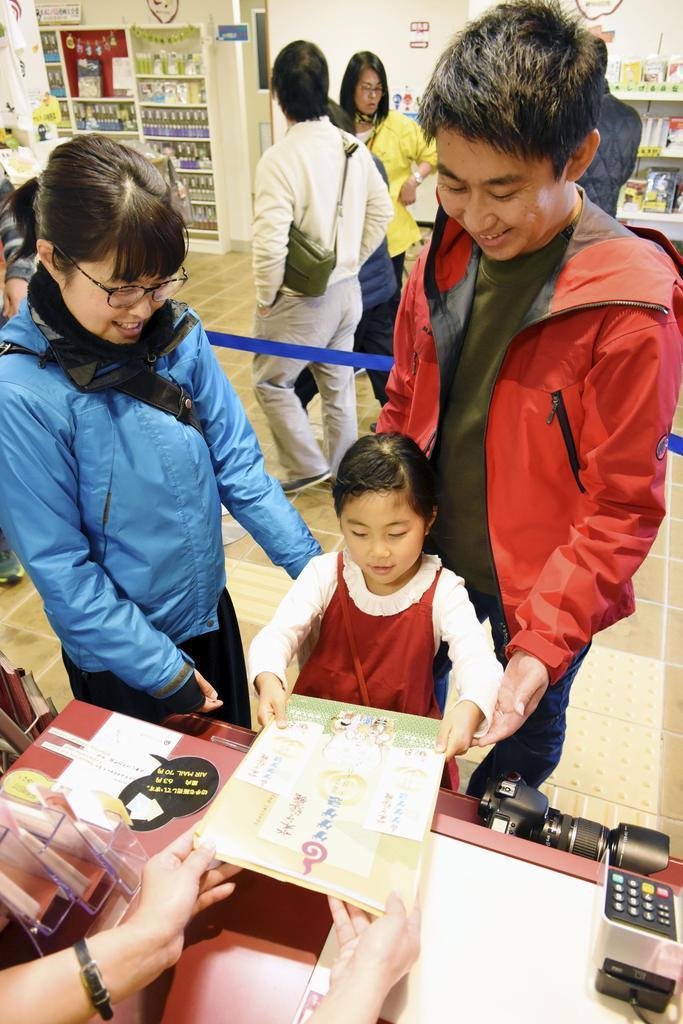 水木しげる記念館で配られた「ゲゲゲ忌」の特別入場券と記念品を受け取る女の子=30日、鳥取県境港市