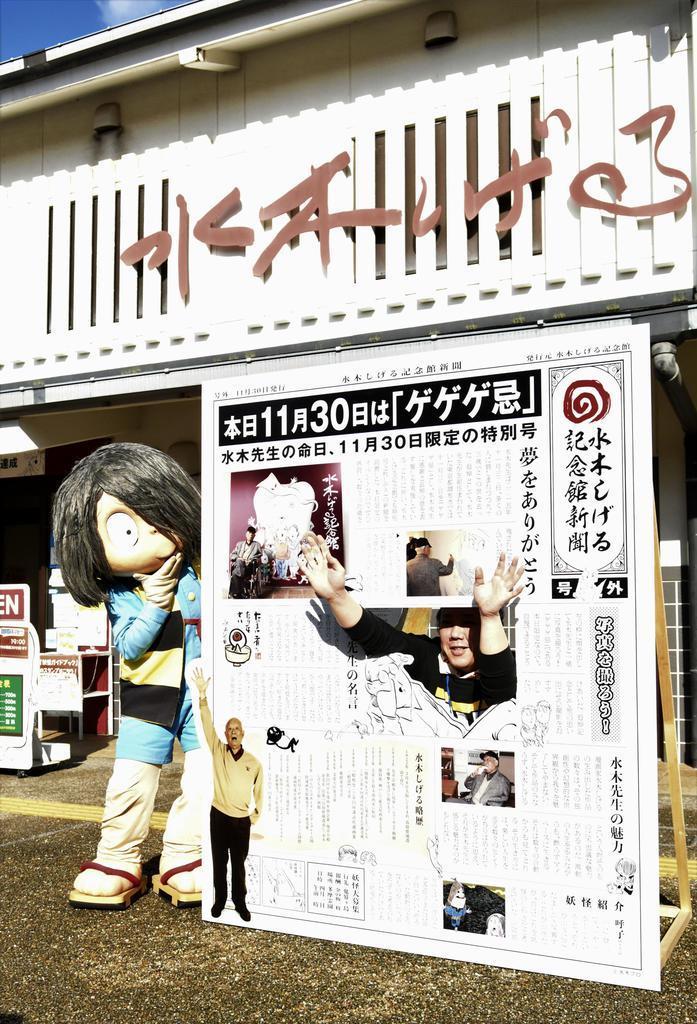 水木しげる記念館前に置かれた「ゲゲゲ忌」のパネルと記念撮影する鬼太郎ら=11月30日、鳥取県境港市
