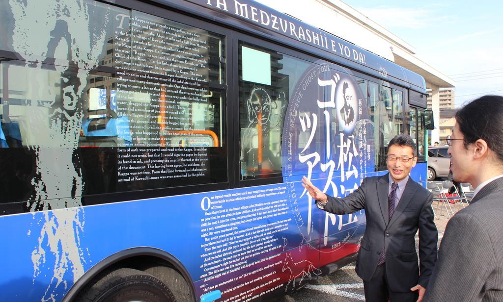 ゴーストツアーのラッピングバス完成を喜ぶ小泉凡さん(左)ら=松江市役所