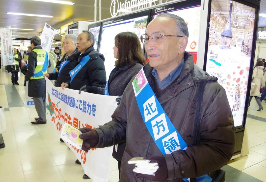 街頭で北方領土返還要求運動への協力を呼び掛ける野口繁正さん(右)=1日午前、JR札幌駅西コンコース