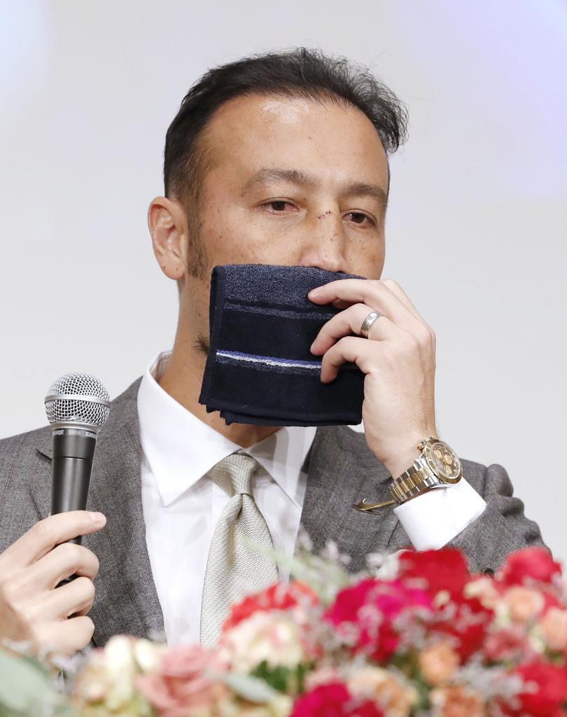 現役引退発表の記者会見で、ハンカチを顔に当てるJ2京都の田中マルクス闘莉王=1日、東京都内のホテル