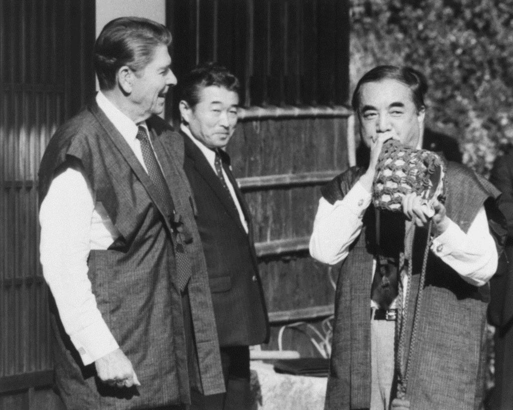 レーガン元米大統領(左)の横で法螺貝を吹く中曽根元首相=昭和58年11月、東京(共同・ロイター)