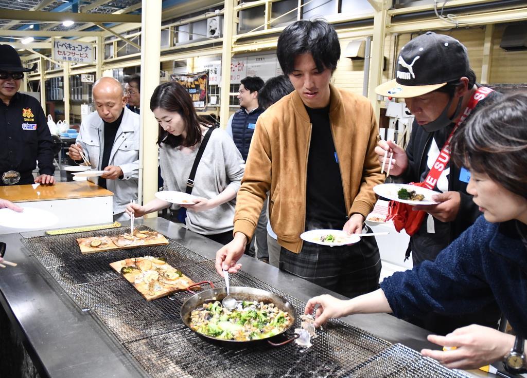 できあがった海鮮バーベキューの料理に舌鼓を打つ漁業関係者ら=11月13日、大阪府田尻町