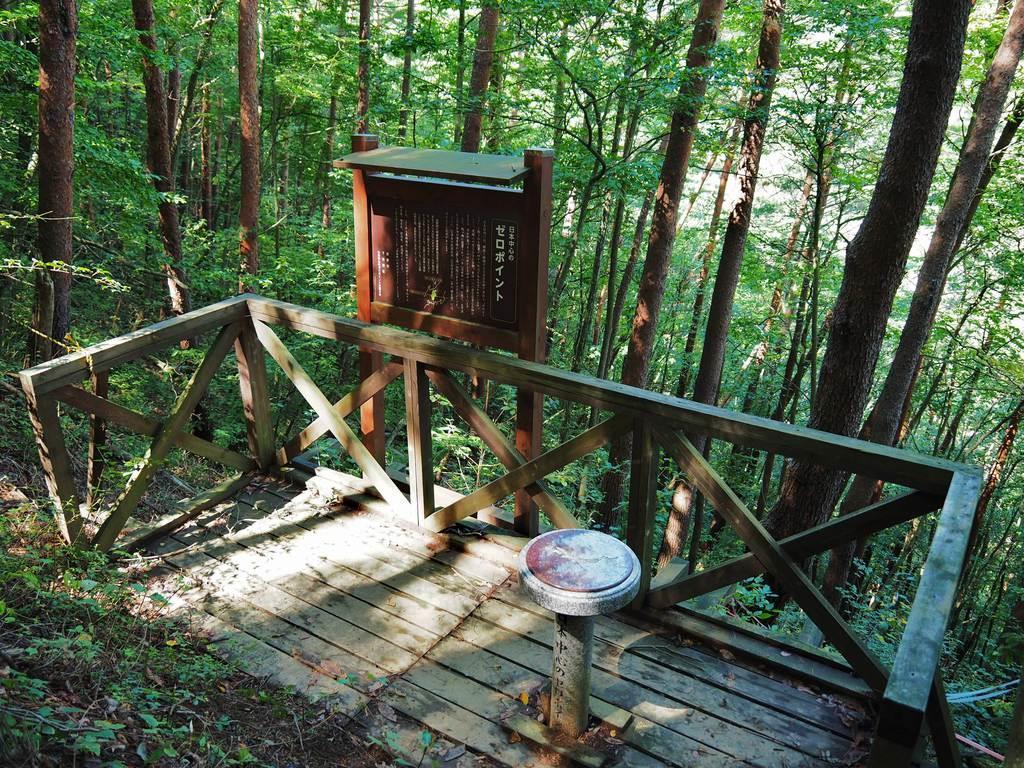 長野県辰野町の大城山山頂付近に位置するゼロポイント地点にはウッドデッキが設えられ、標柱が建っている。もともとは木製で「日本の地理的中心」と記されていたが、現在はコンクリート製になり、「日本中心のゼロポイント」と改めた(同町提供)