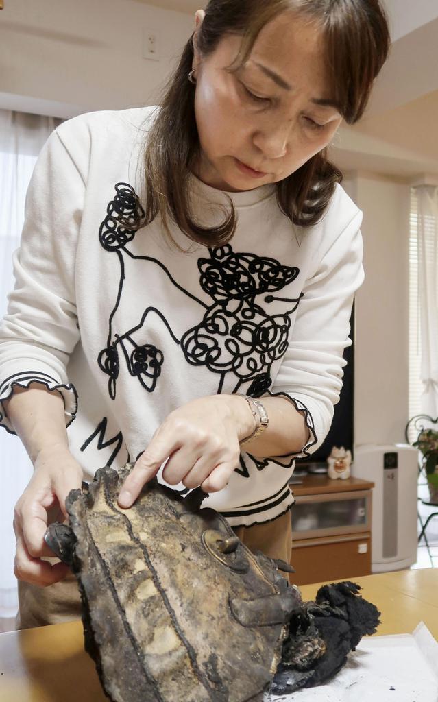 犠牲となった石川友梨さんの遺品のかばんを手に取る母佳子さん=11月、神奈川県横須賀市