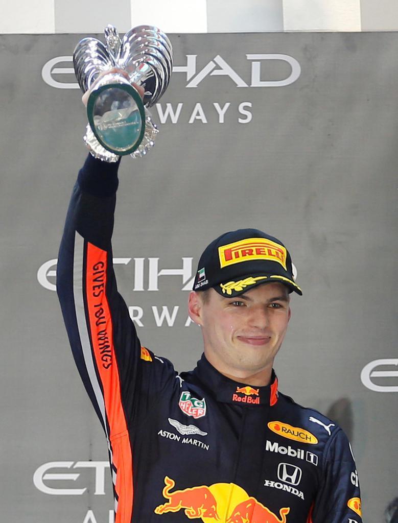自動車F1アブダビGPで2位となり、表彰台で笑顔を見せるマックス・フェルスタッペン=アブダビ(ロイター)