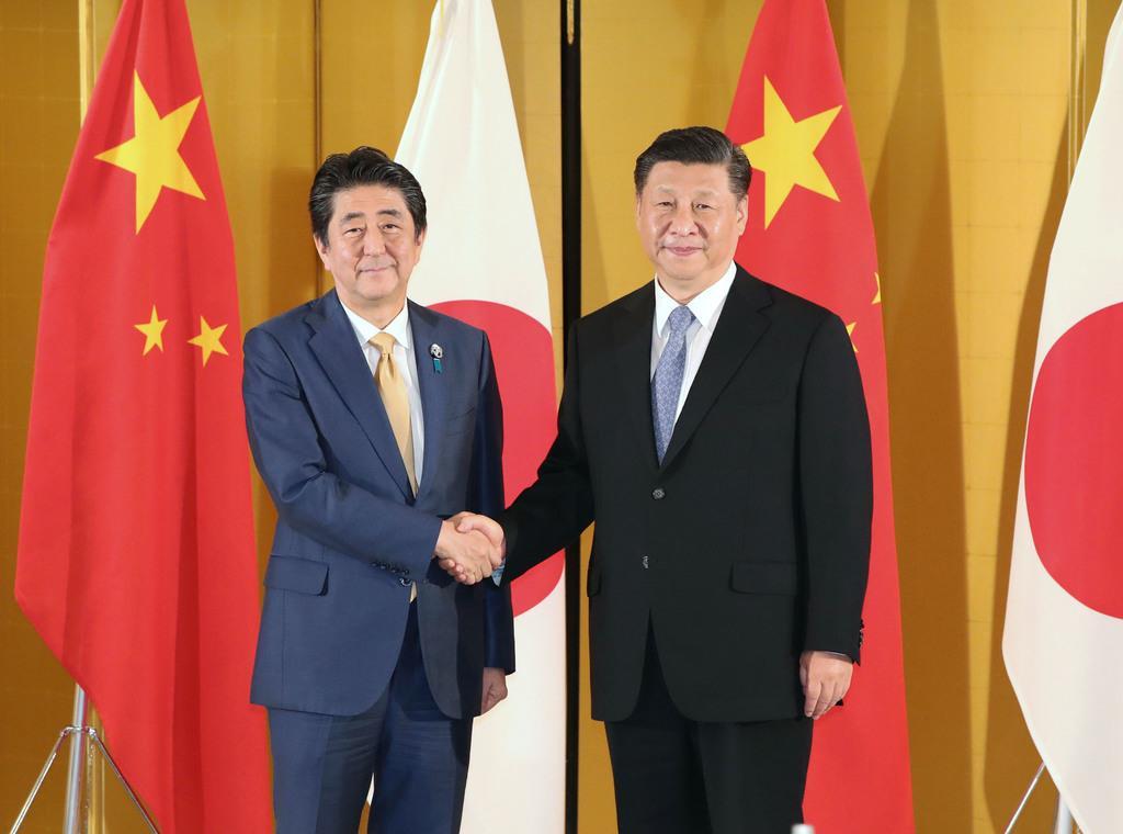 中国の習近平国家主席(右)と握手する安倍首相=6月、大阪市内のホテル