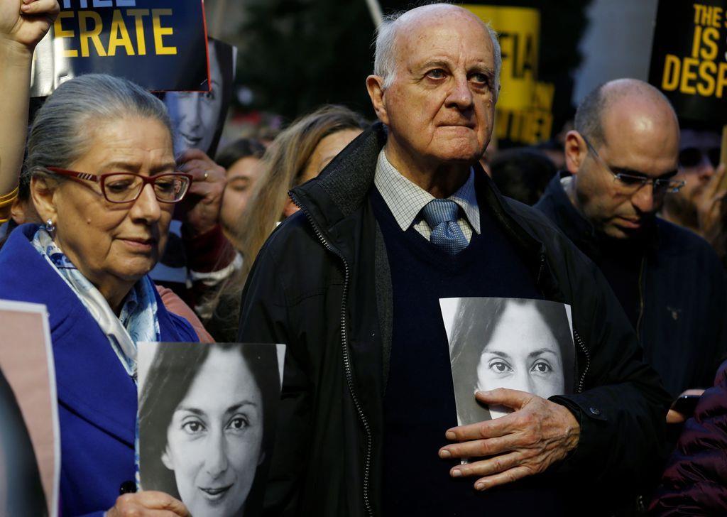 殺害された女性記者、ダフネ・カルアナガリチアさんの遺影を抱えて裁判所前のデモに参加する両親=1日、マルタの首都バレッタ(ロイター)