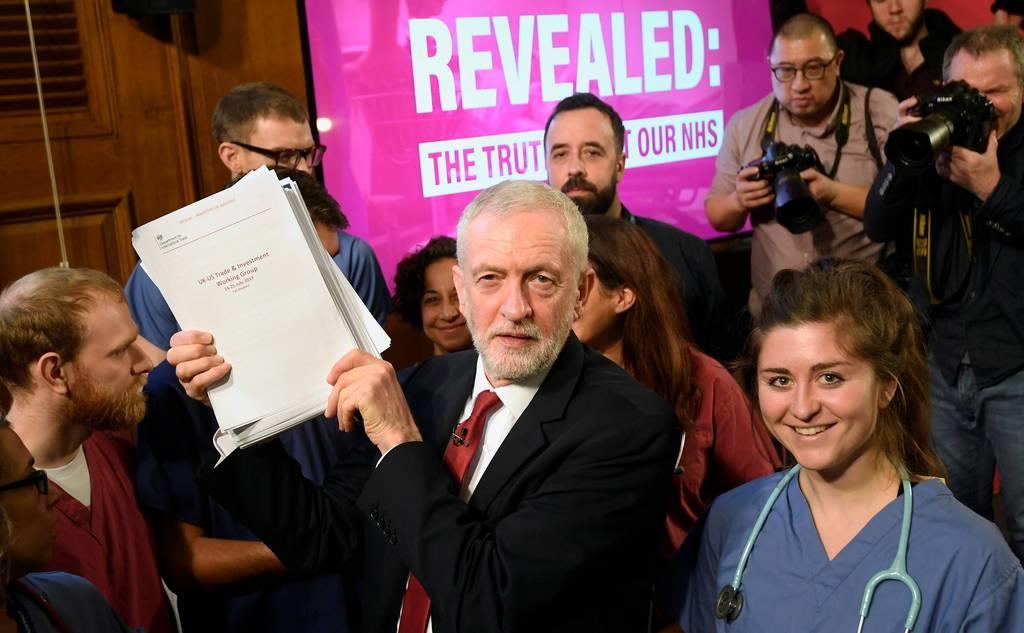 11月27日、ロンドンで選挙公約の文書を手に選挙運動する労働党のコービン党首(ロイター)