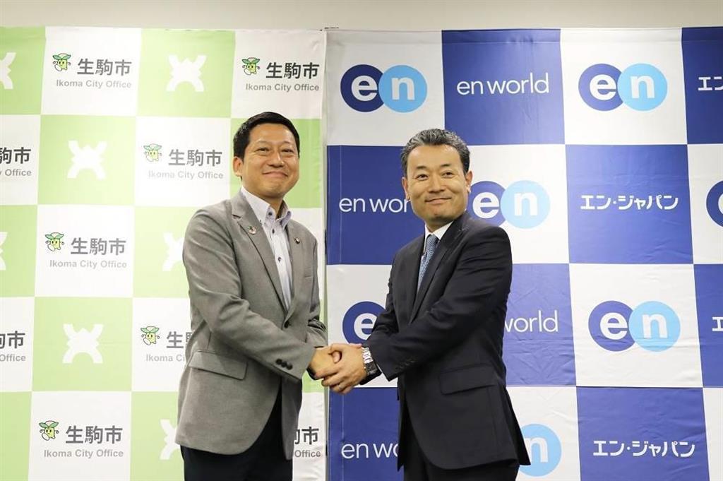 エン・ジャパンと連携協定を結び、同社の鈴木孝二社長(右)と握手を交わす小紫雅史市長(同社提供)