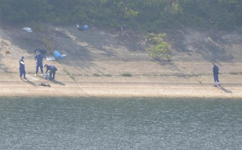 女性の遺体が入った衣装ケースが発見されたダムを調べる捜査員=兵庫県加古川市