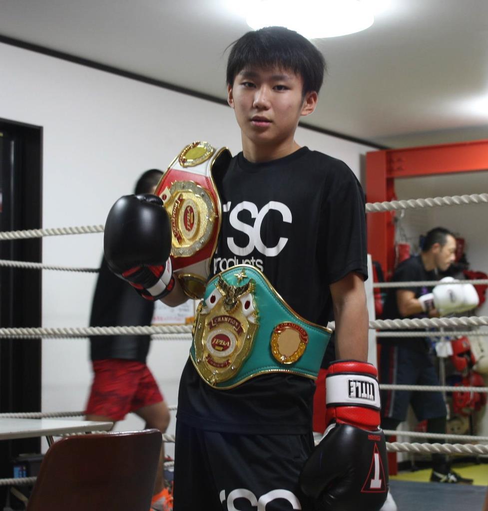 2年連続で獲得したボクシング・ジュニア全国大会優勝のチャンピオンベルトを着けてポーズをとる石川翔さん=野田市(永田岳彦撮影)