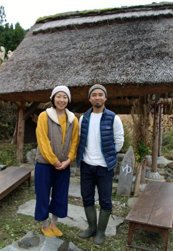 かやぶき屋根の手作り足湯を完成させた前田敦司さん、由香里さん夫妻=豊岡市日高町
