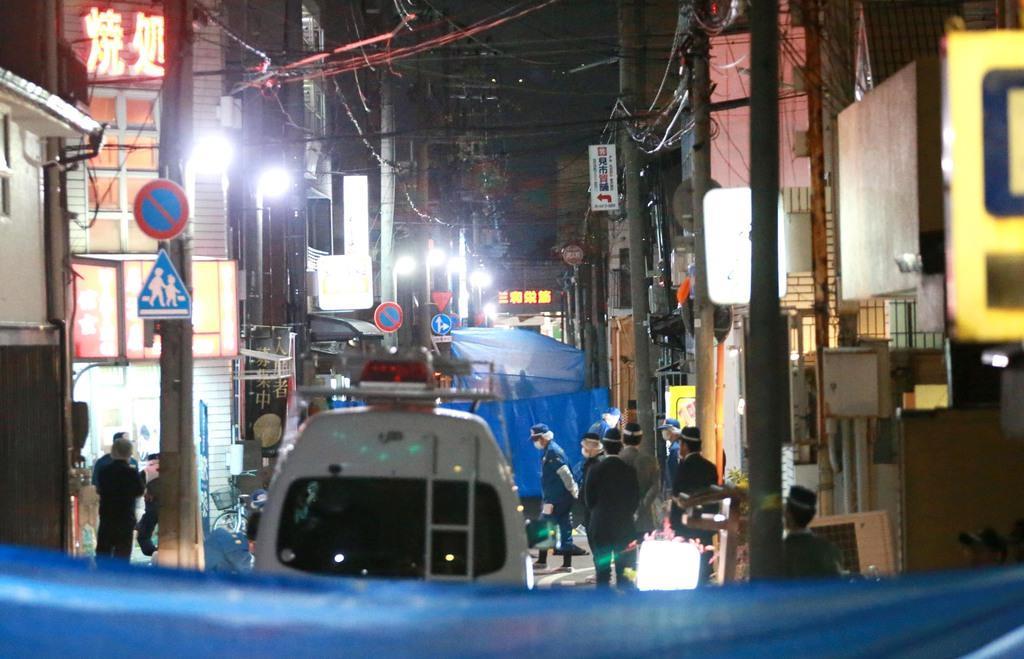 山口組幹部が銃撃された現場付近を調べる警察官ら=27日午後8時8分、兵庫県尼崎市