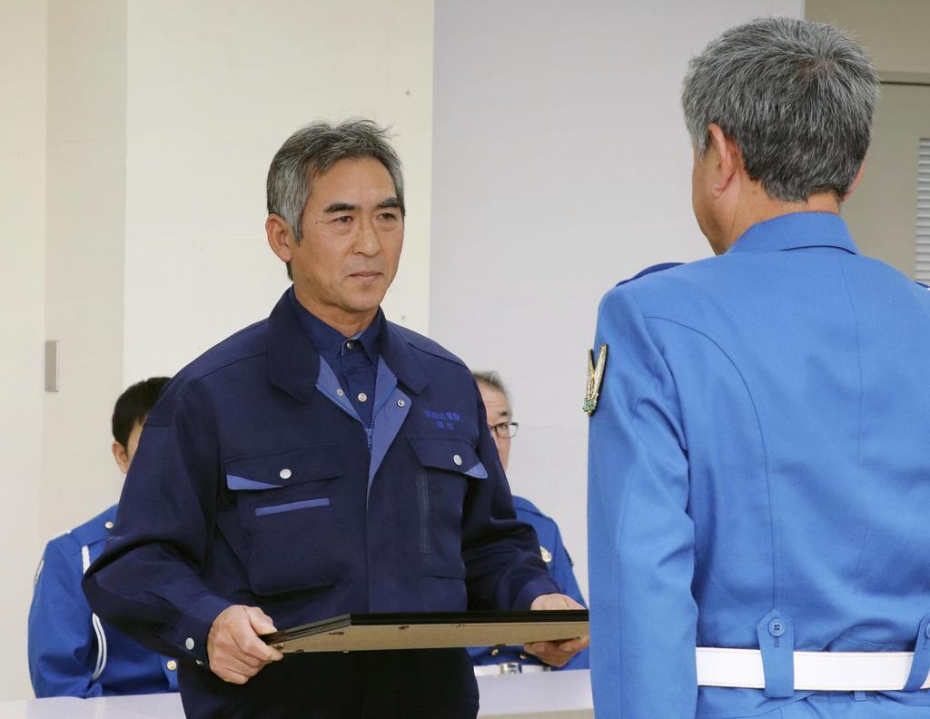 岩手県警高速隊から感謝状を贈られる岡村三八喜さん(左)=4日午前、盛岡市