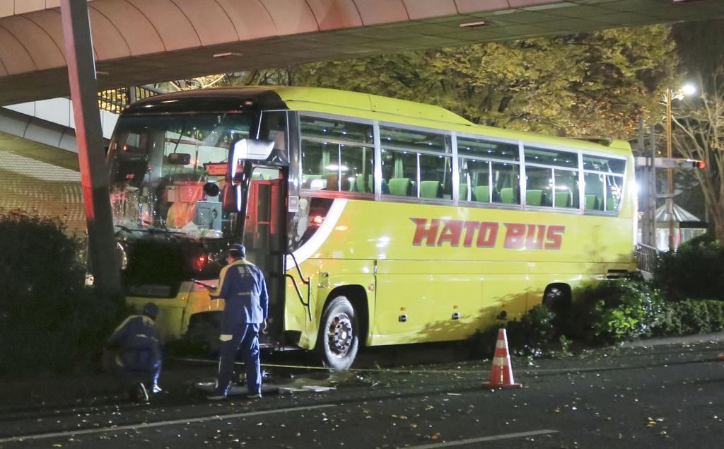 ハイヤーに追突して乗り上げ、街路灯に衝突して止まった「はとバス」の観光バス=4日午後7時58分、東京都新宿区