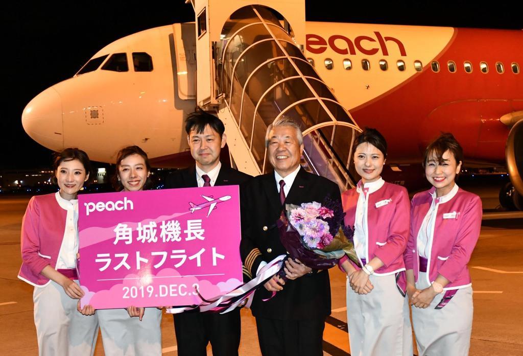 ラストフライトを終え、記念写真に収まる角城健次さん(右から3人目)=3日午後、関西国際空港