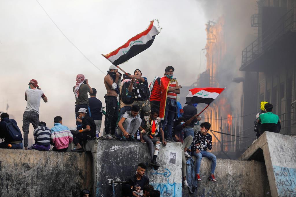 イラクの国旗を掲げる反政府デモの参加者ら=11月30日、バグダッド(ロイター)