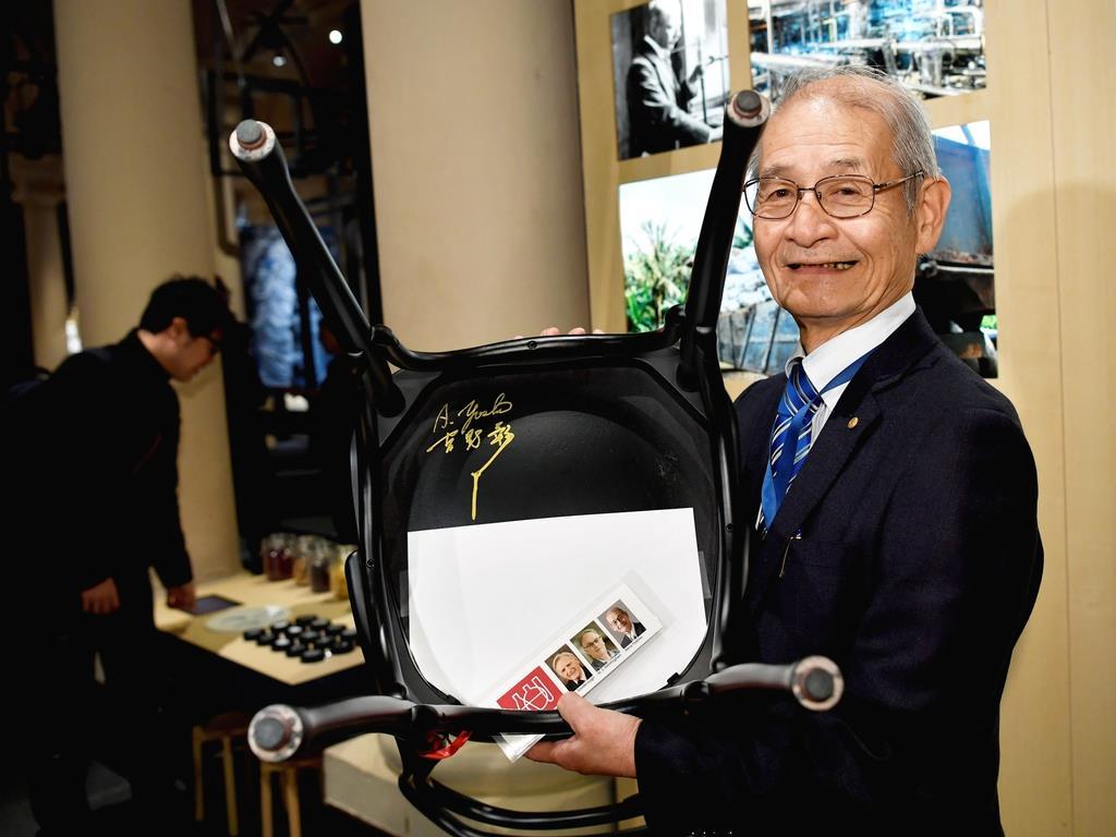ストックホルムのノーベル博物館でサインした椅子を持つ吉野彰・旭化成名誉フェロー=6日(ロイター)