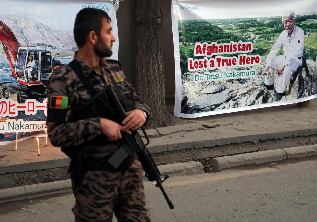 殺害された医師中村哲さんのポスターの前に立つアフガニスタンの治安部隊要員。ポスターには「アフガニスタンは真の英雄を失った」と書かれている=5日、カブール(ロイター)