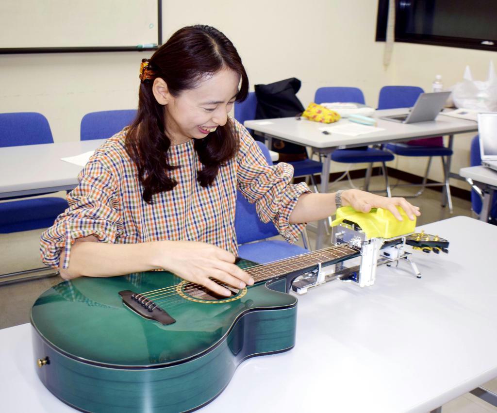 開発を手掛けた補助装置を付け、ギターを演奏する西ノ平志子さん