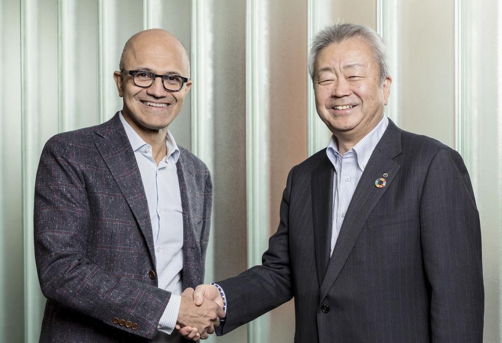 マイクロソフトの最高経営責任者(左)と握手するNTTの澤田純社長=9日、米ワシントン州のマイクロソフト本社(NTT提供)