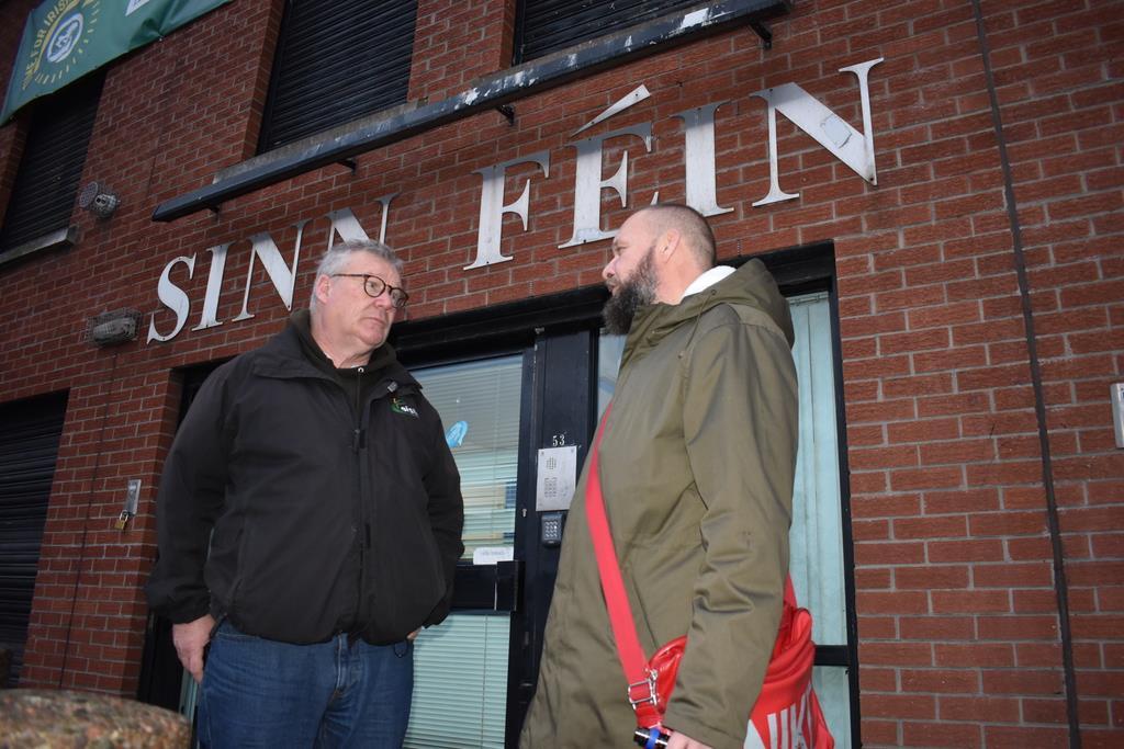 ベルファストのシン・フェイン党の事務所前で元IRA民兵の男性と話す元英国兵士のリー・ラビスさん(右)=板東和正撮影
