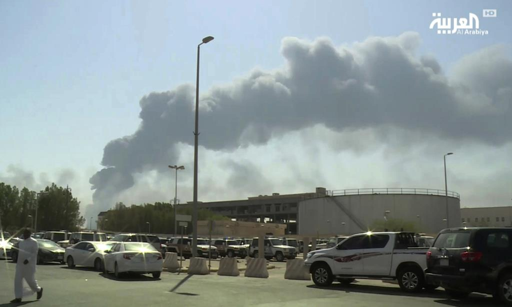 攻撃され、煙を上げる石油施設=9月14日、サウジアラビアのアブカイク(Al-Arabiya・AP)