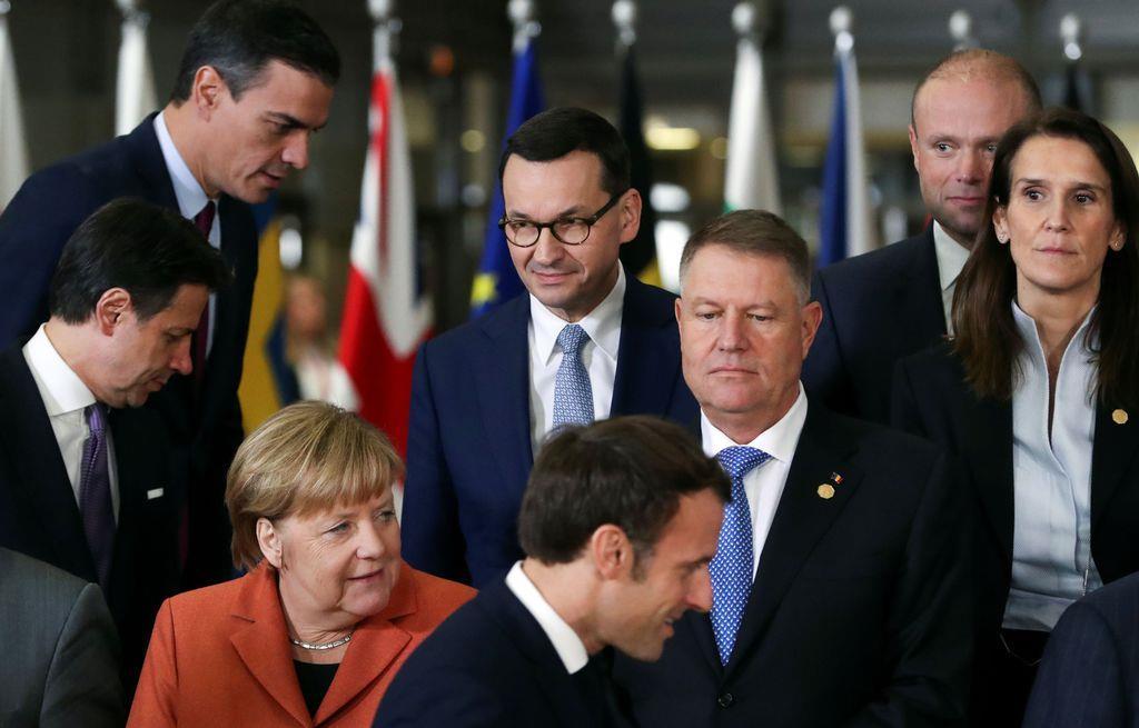 ドイツのメルケル首相らEU各国首脳と一緒に記念撮影を待つポーランドのマテウシュ・モラヴィエツキ首相(中央後列)=12日、ブリュッセル(ロイター)