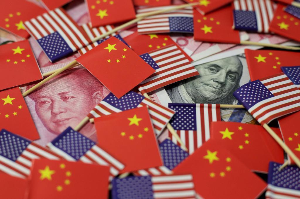 人民元、ドル紙幣と米中の国旗。中国投資は米中摩擦の影響が続いた(ロイター)