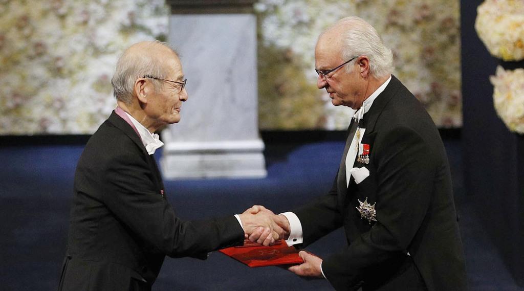 スウェーデンのカール16世グスタフ国王(右)からノーベル化学賞のメダルと賞状を授与される吉野彰・旭化成名誉フェロー=10日、ストックホルムのコンサートホール(共同)