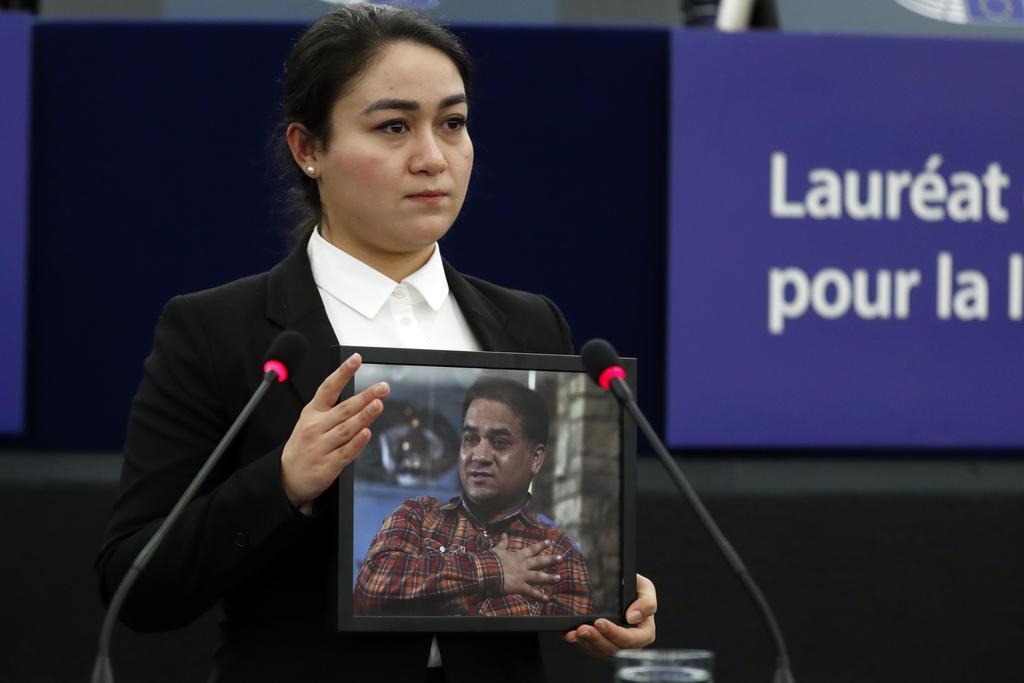 18日、サハロフ賞の授賞式で、受賞者イリハム・トフティ氏の写真を掲げ、代理出席する娘のジュハル氏=フランス・ストラスブール(AP)