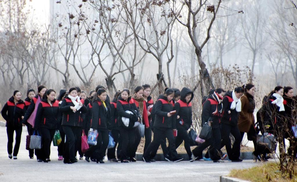 17日早朝、中国遼寧省丹東の工業団地で、隊列を組んで宿舎から工場へ出勤する北朝鮮の労働者ら(西見由章撮影)