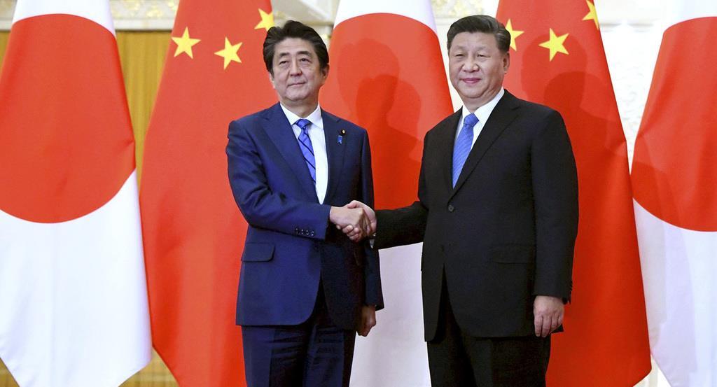 中国の習近平国家主席(右)と握手する安倍晋三首相=23日、北京の人民大会堂(AP)