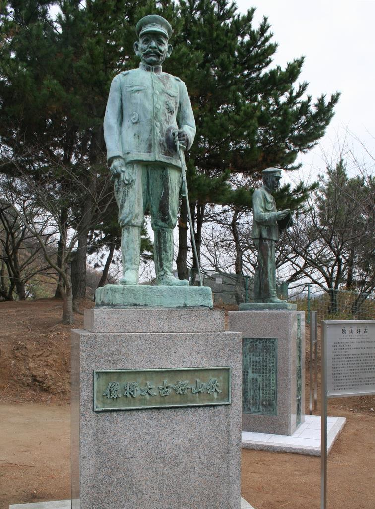 秋山好古の像(左)と、そばに移築された真之の像=松山市梅津寺町