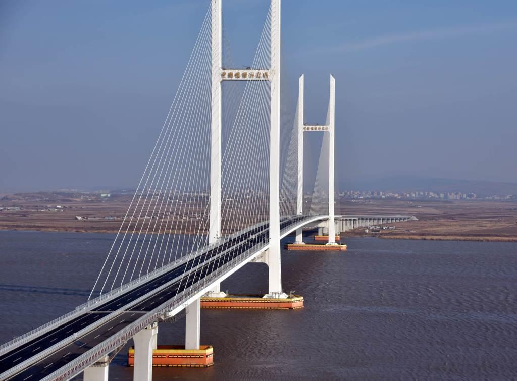 中国遼寧省丹東と北朝鮮新義州を結ぶ「新鴨緑江大橋」。写真奥の北朝鮮側で道路整備が進んでいる(西見由章撮影)
