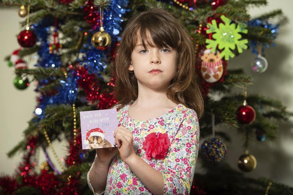テスコで買ったクリスマスカードを手にする少女。購入した束の1枚に、中国から助けを求めるメッセージが書かれていた=22日、ロンドン(AP)