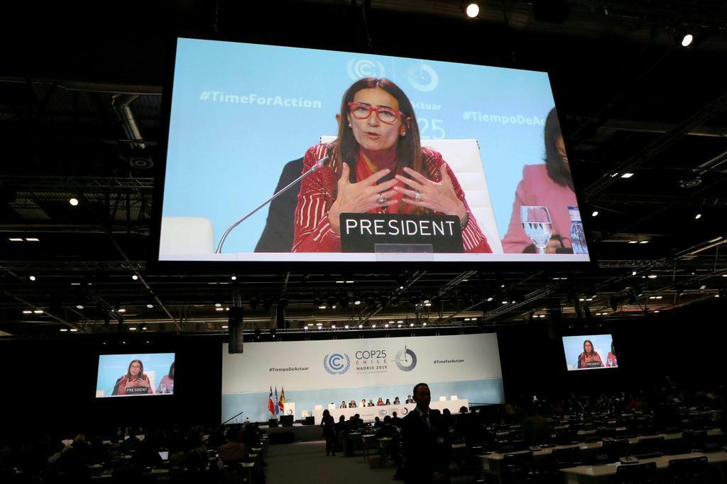 15日、COP25で大画面に映された議長国チリのシュミット環境相(ロイター)