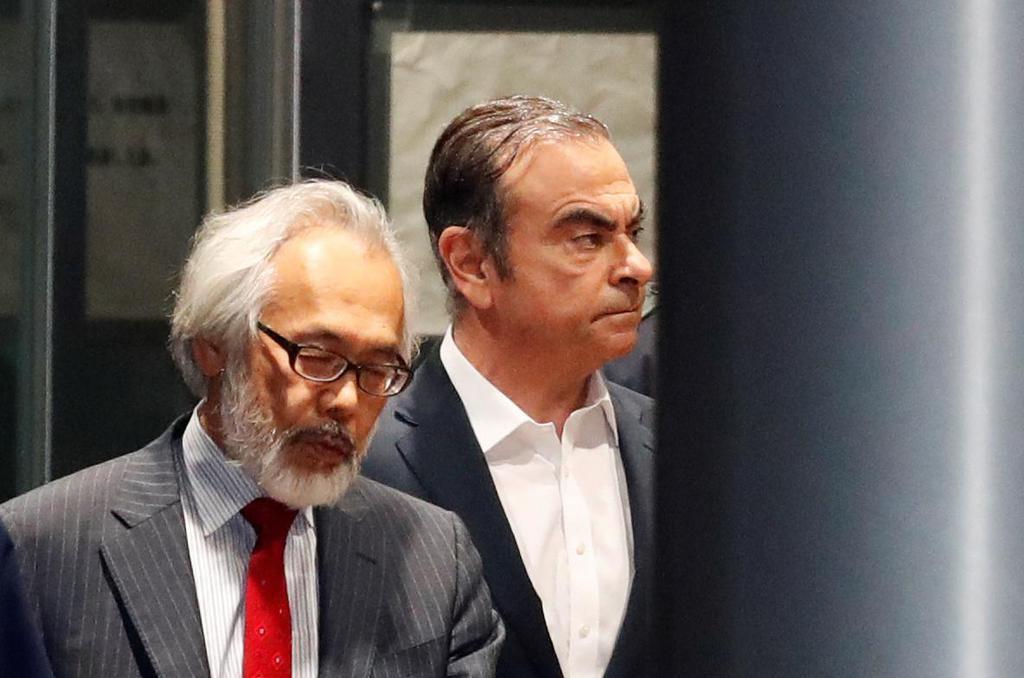 東京都内の住宅から出る前日産自動車会長カルロス・ゴーン被告(右)=2019年4月25日(ロイター)