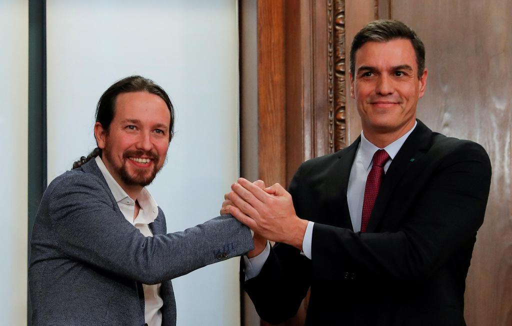 スペインの急進左派政党ポデモス党首と手を取り合うサンチェス首相(右)=2019年12月30日、マドリード(ロイター)