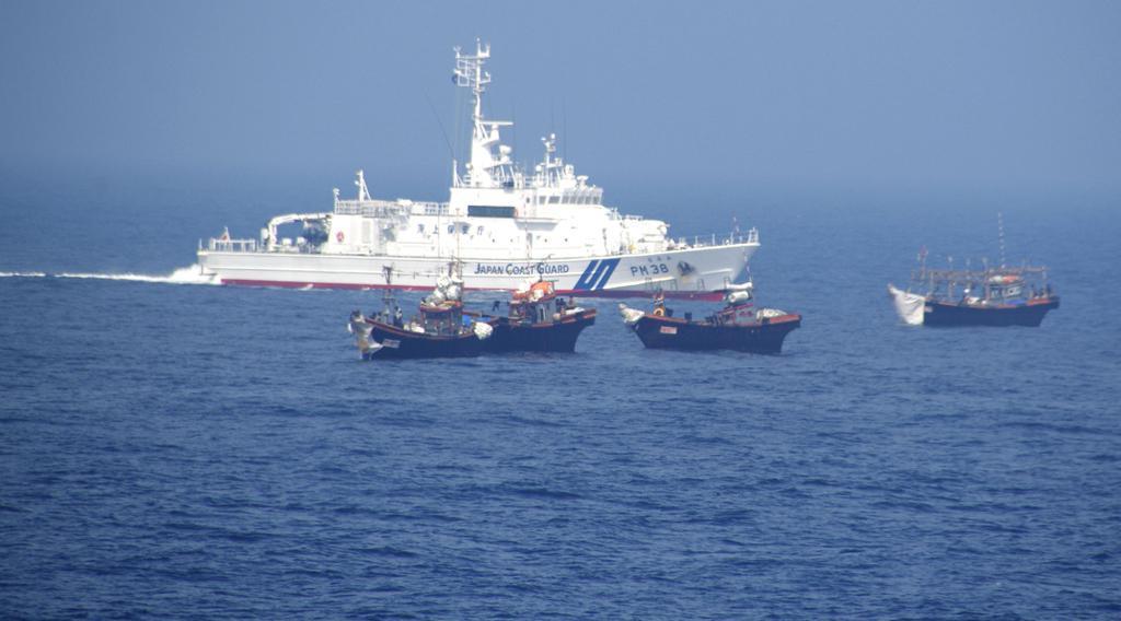 日本海の大和堆周辺で北朝鮮漁船に退去警告をする海上保安庁の巡視船(奥)=2019年6月中旬(同庁提供)