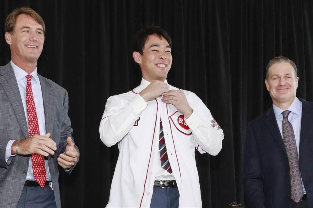 米大リーグ、レッズの入団会見でユニホームに袖を通し、笑顔を見せる秋山翔吾外野手(中央)=8日、米シンシナティ(共同)