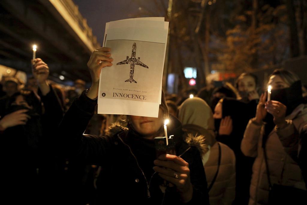 航空機の資料を掲げて、墜落犠牲者を悼むイランの人たち=11日、テヘラン(AP)
