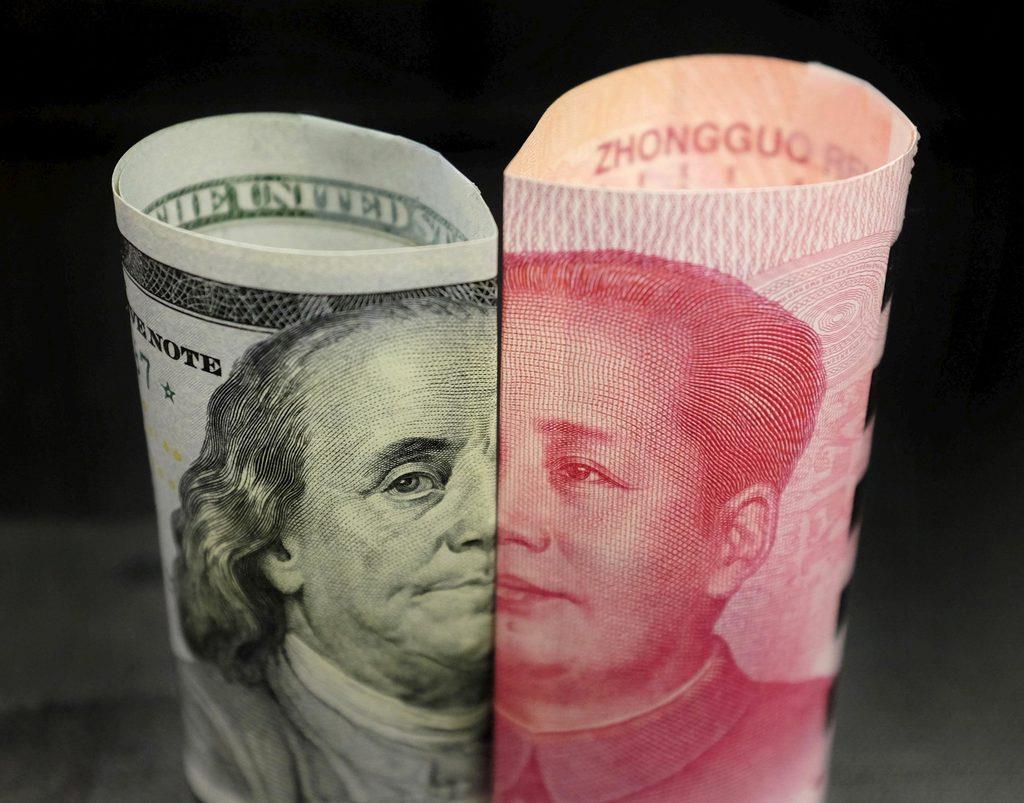 100ドル札(左)と100元札=2016年1月、北京(ロイター)