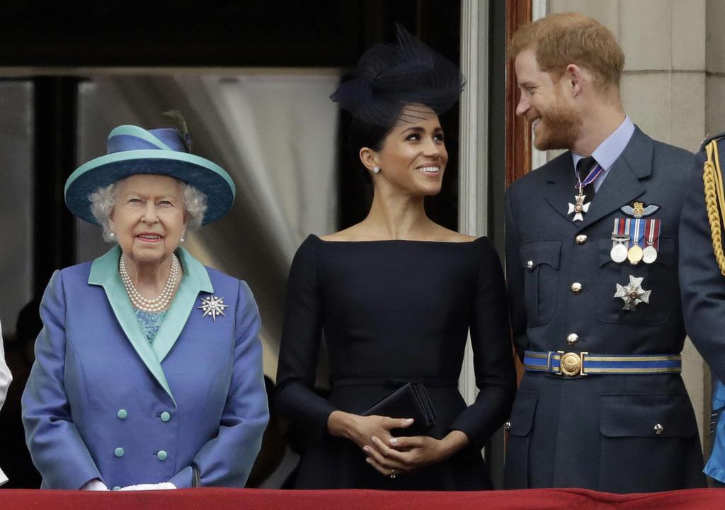 エリザベス女王(左)と並んで立つメーガン妃(中央)とヘンリー王子=2018年7月、ロンドン(AP)